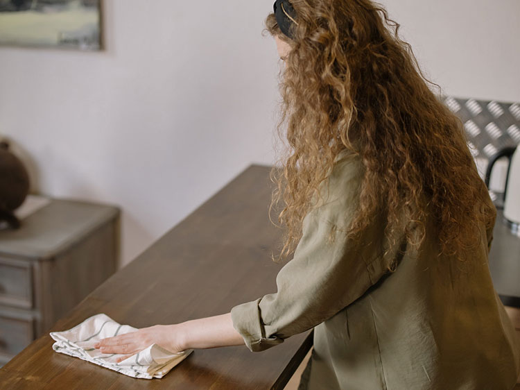 Kobieta czyszcząca meble kuchenne