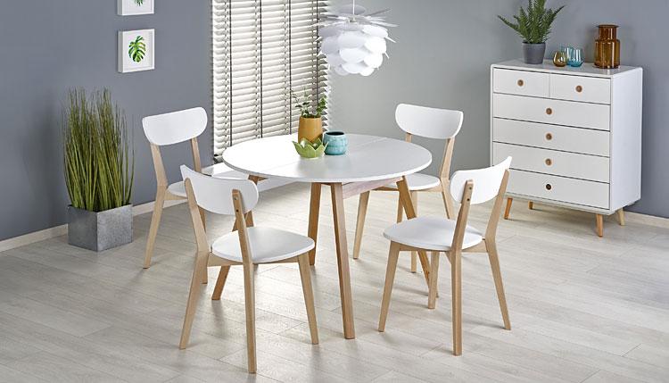 stół w stylu skandynawskim z białym blatem ustawiony w centralnej części salonu