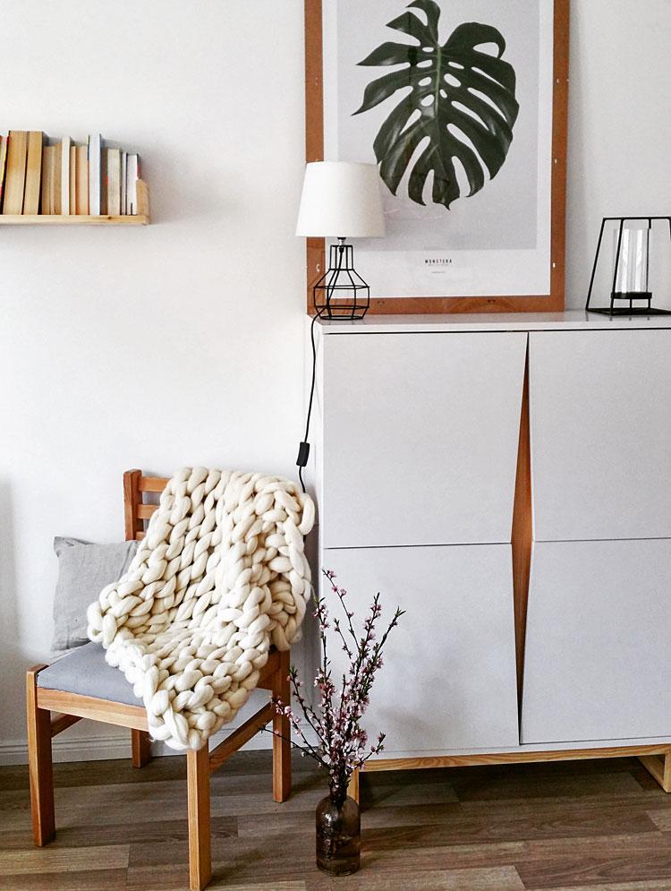 plakat w ramce oraz lampka ustawione na białej komodzie skandynawskiej