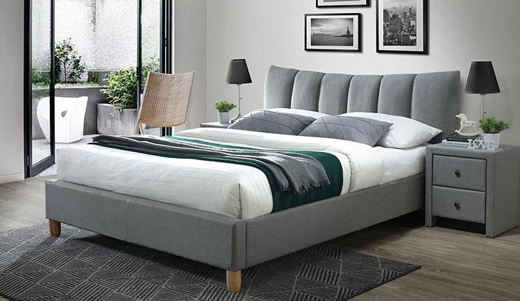 tapicerowane łóżko ustawione przy wyjściu na balkon w sypialni