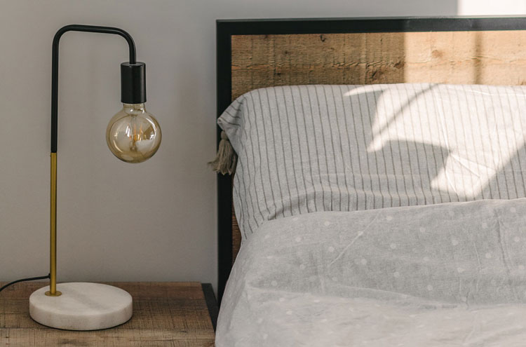 lampka nocna przy łóżku w małej sypialni